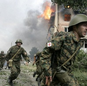 Soldiers run near a blazing apartment after a bombardment in the town of Gori, 80 km (50 miles) from Tbilisi, August 9, 2008. A Russian warplane dropped a bomb on an apartment block in the Georgian town of Gori on Saturday, killing at least 5 people, a Reuters reporter said. The bomb hit the five-story building in Gori close to  Georgia's embattled breakaway province of South Ossetia when Russian warplanes carried out a raid against military targets around the town.   REUTERS/David Mdzinarishvili (GEORGIA)